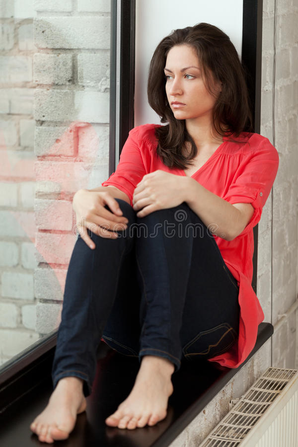 Morning on windowsill. Girl sitting on windowsill and looking in the window royalty free stock photos