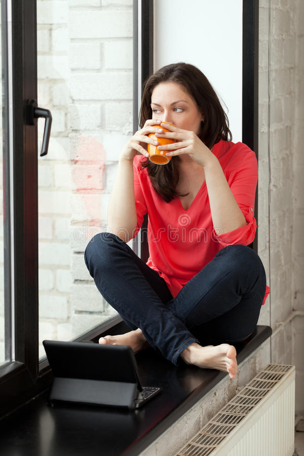Morning on windowsill. Girl sitting on windowsill with cup of tee and notebook stock image