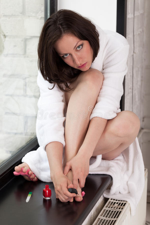 Morning on windowsill. Girl in bathrobe making manicure and pedicure royalty free stock photos