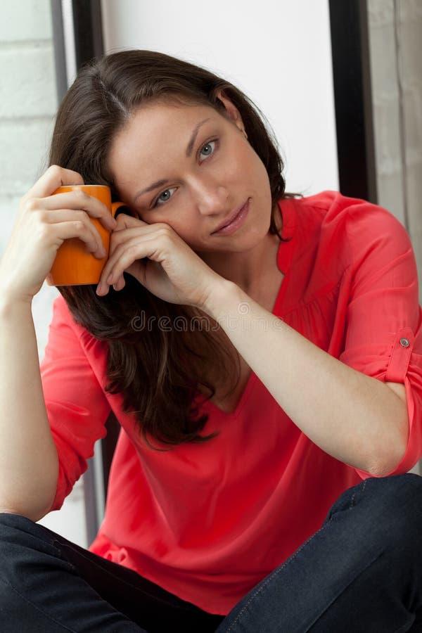 Morning on windowsill. Girl sitting on windowsill with cup of tee stock image