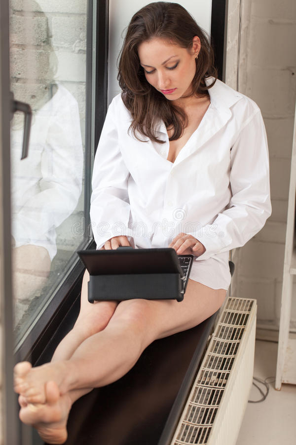 Morning on windowsill. Female sitting on windowsill and typing an e-mail royalty free stock photos