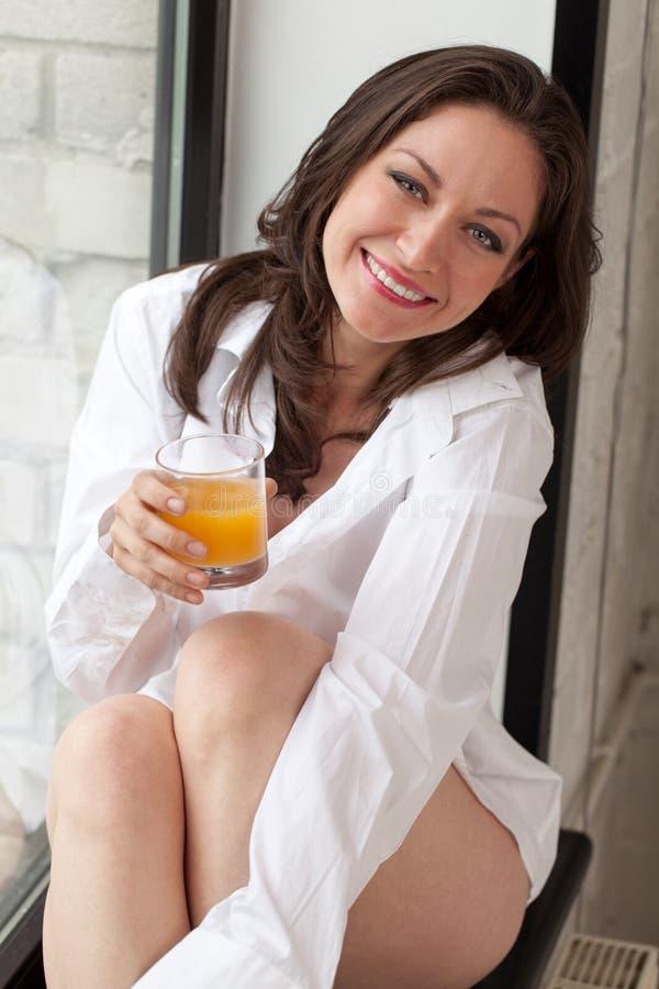Morning on windowsill. Smiling girl with glass of juice sitting on windowsill stock image