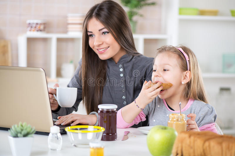 Morning before work. Business Woman and her daughter breakfast in the kitchen. Little girl eats bread with peanut butter. Beautiful young Business women drinking royalty free stock photography