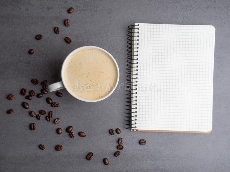 Morning workplace as cup of coffee, coffee beans and notepad for notes. Minimalism concept royalty free stock images