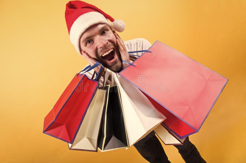The morning before Xmas. man in santa hat hold christmas present. delivery christmas gifts. happy santa man on yellow royalty free stock photography