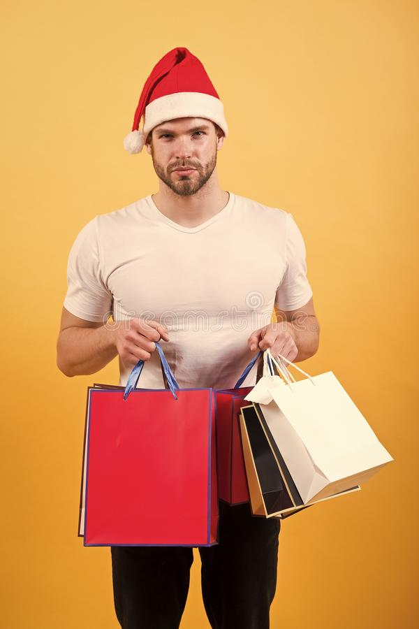 The morning before Xmas. man in santa hat hold christmas present. delivery christmas gifts. happy santa man on yellow. Background. online christmas shopping royalty free stock photography