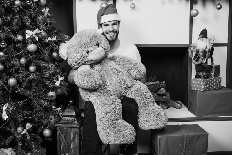 The morning before Xmas. man in santa hat hold christmas present. online christmas shopping. New year scene. happy santa. Man with bear toy. delivery christmas stock image