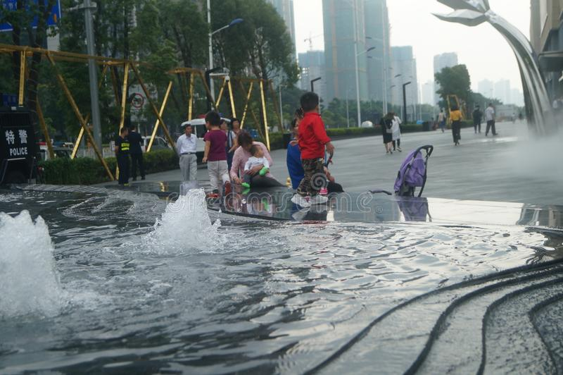 Shenzhen, China: adults and children play around the fountain in the shopping mall. In the morning, Yi Fang Cheng shopping mall fountain pool, adults and royalty free stock photos