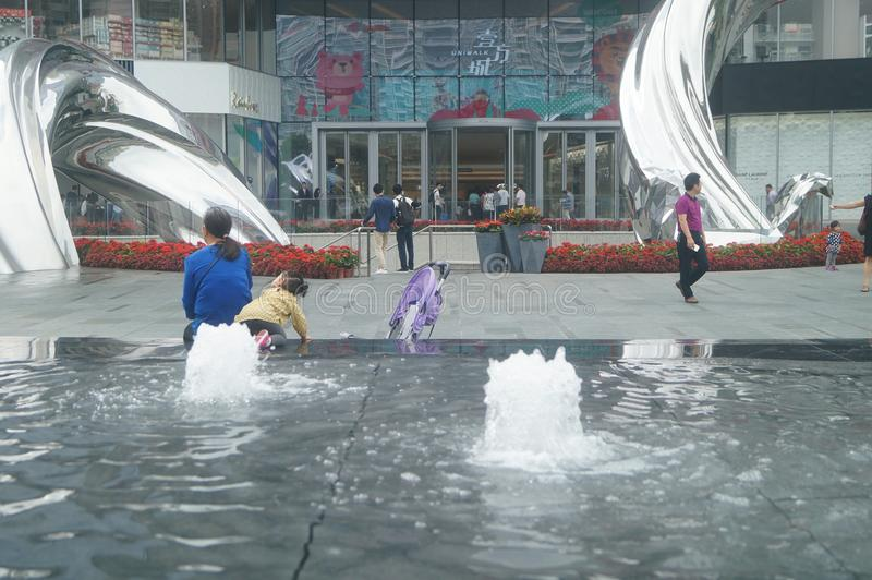 Shenzhen, China: adults and children play around the fountain in the shopping mall. In the morning, Yi Fang Cheng shopping mall fountain pool, adults and stock images
