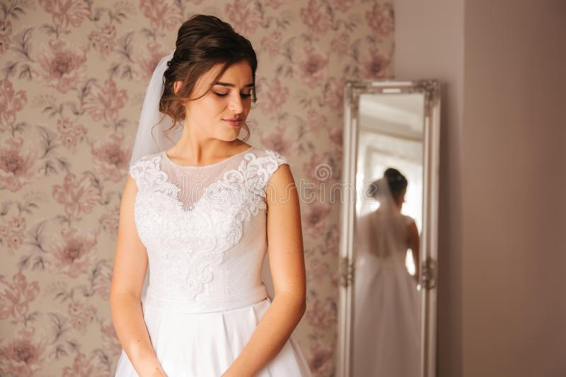 Morning of young bride. Portrait of beautiful girl. White wedding dress stock images
