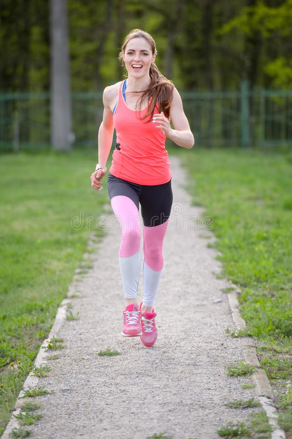 Morning of young sporty woman running outdoors in the park royalty free stock photography