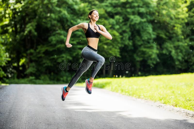 Morning of young fitness woman running outdoors in the park royalty free stock photography