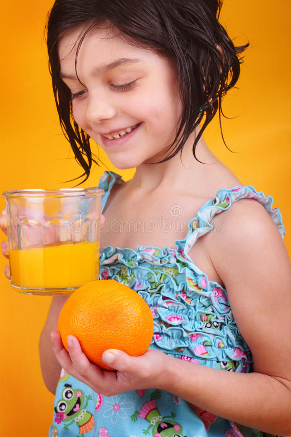 Mornings and Orange Juice. A cute little dark haired girl gazing into a glass of fresh squeezed orange juice, holding a fresh orange on orange background stock photography