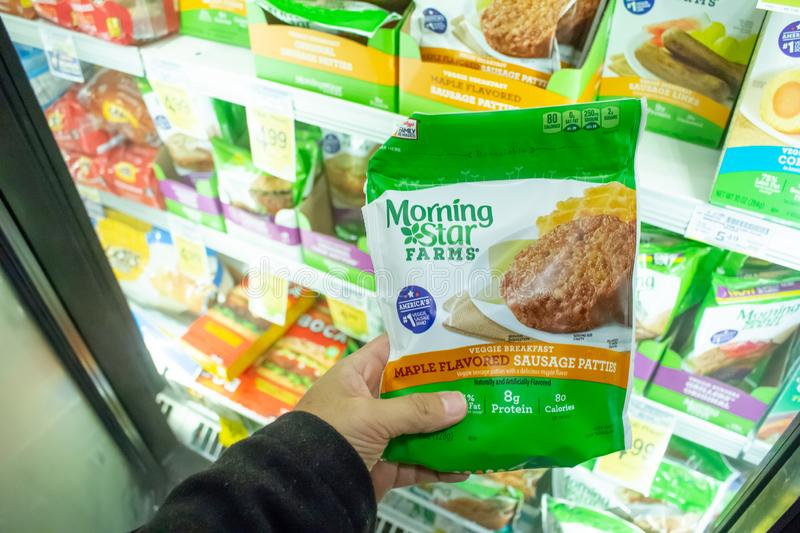 MorningStar Farms products. A hand holds package of MorningStar Farms breakfast sausage, standing at the freezer section of a local grocery store royalty free stock photo