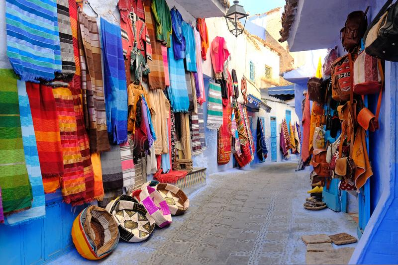 Moroccan handmade crafts, carpets and bags hanging in the narrow street of Essaouira in Morocco with selective focus stock photo