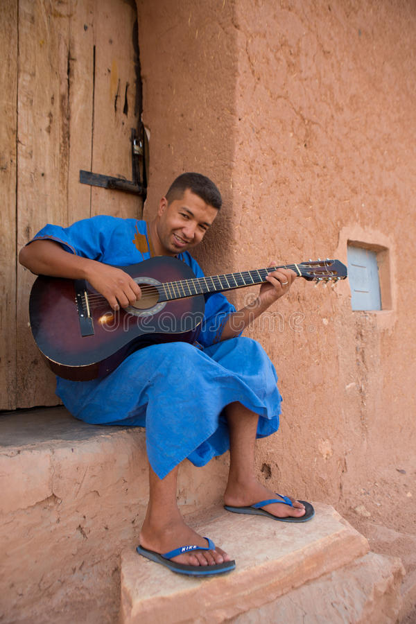 Moroccan man musician playing guitar, Morocco. AIT BEN HADDOU, MOROCCO, AUGUST 31: Portrait of Moroccan man musician playing guitar and wearing the traditional stock photos