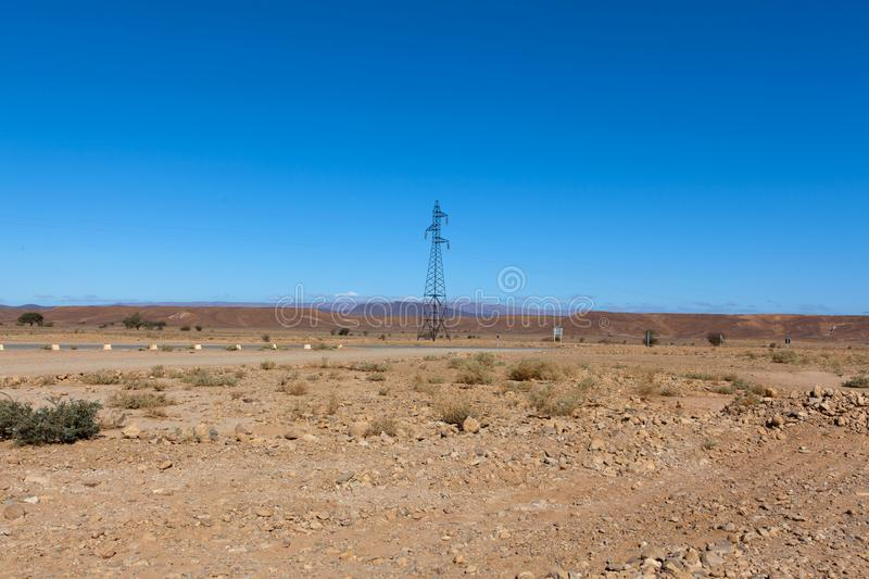 Moroccan rocky desert landscape with plants and mountain range royalty free stock photos