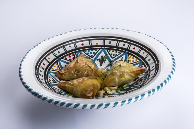 Moroccan sweet cookies made with warqa dough stuffed with a mass of almonds. In a ceramic dish with a colorful decoration, delicious sweet cookies stock photo