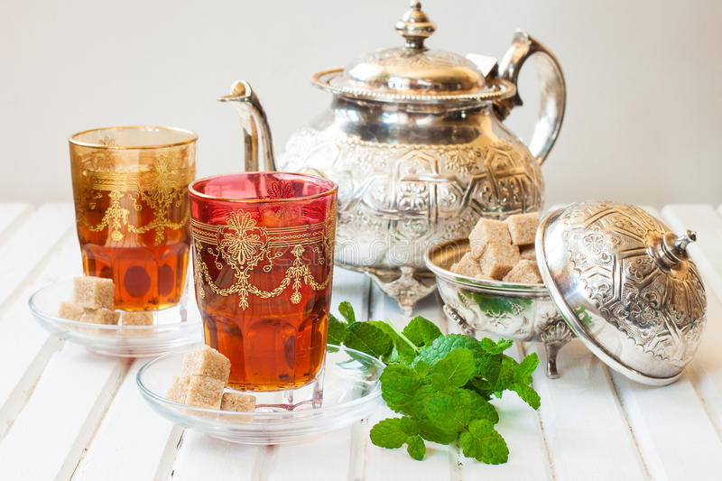 Moroccan tea with mint and sugar in a glass on a white table with a kettle stock images