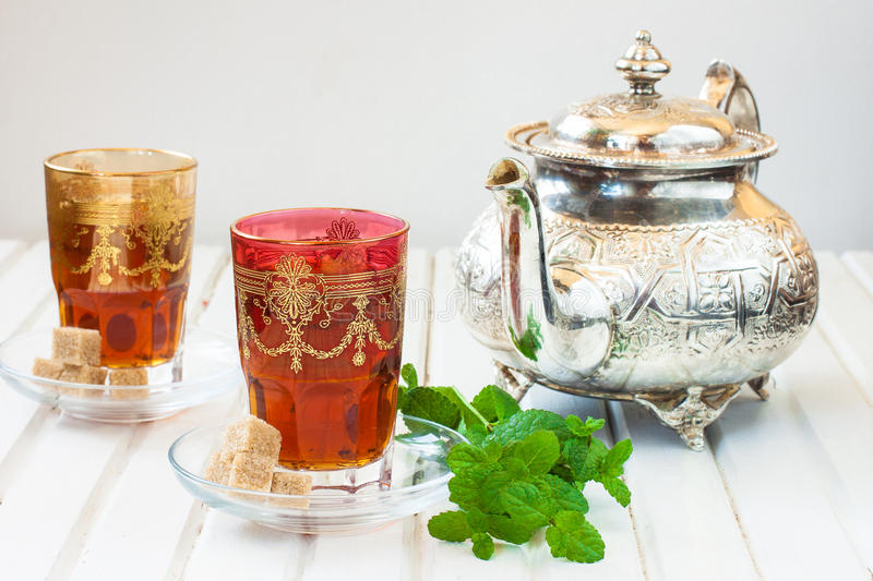 Moroccan tea with mint and sugar in a glass on a white table with a kettle stock photo