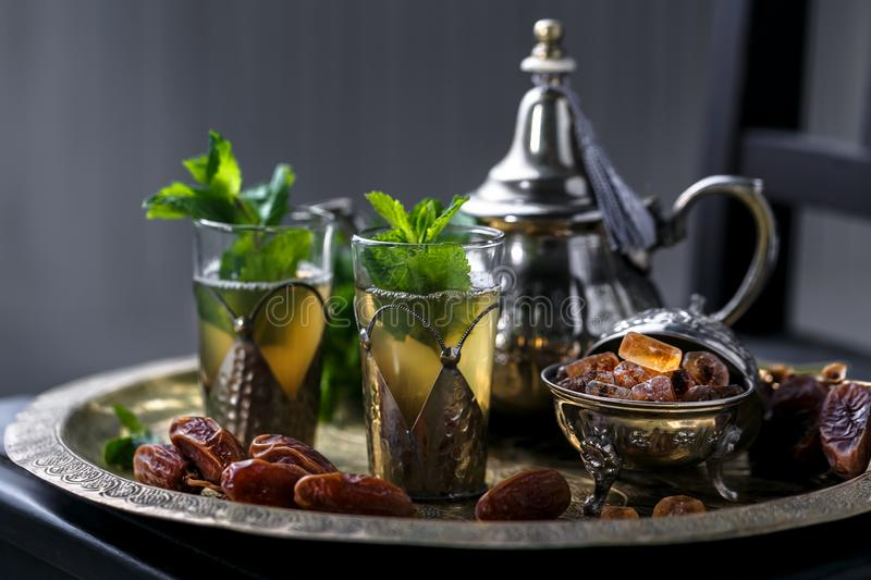 Moroccan tea with mint in traditional glasses, teapot and sugar. On copper plate royalty free stock photos