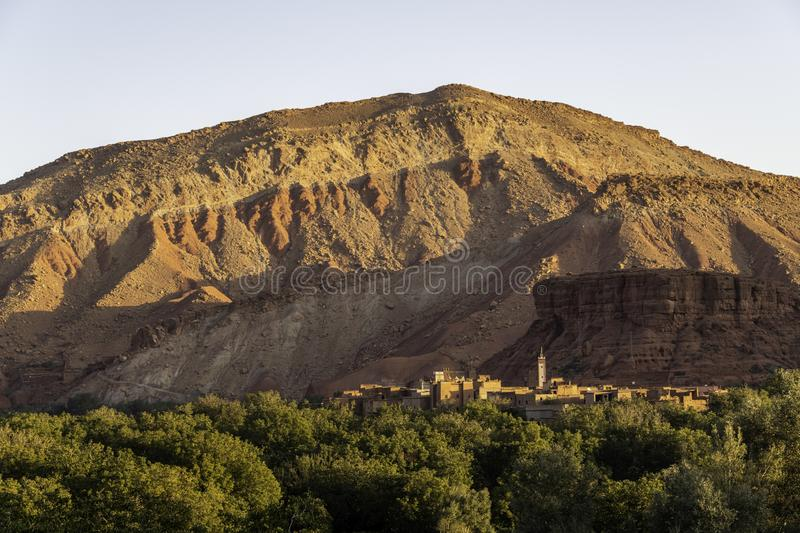 Moroccan village with mountains, river, desert, mountains and lush vegetation near sunrise stock photo