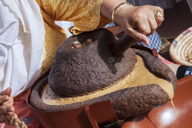 Moroccan woman grinding argan kernels traditionally with a mills royalty free stock photography