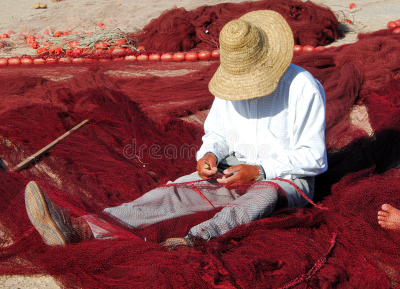 Morocco, Essaouira: fisherman. Repairing his red fishing net by a sunny day stock photos