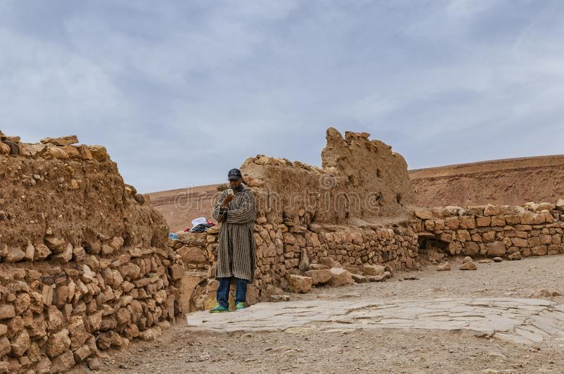 Morocco, Kasbah Ait Ben Haddou near Ouarzazate in the Atlas Mountains , 28 March 2018, Moroccan man leaning against a wall and royalty free stock images