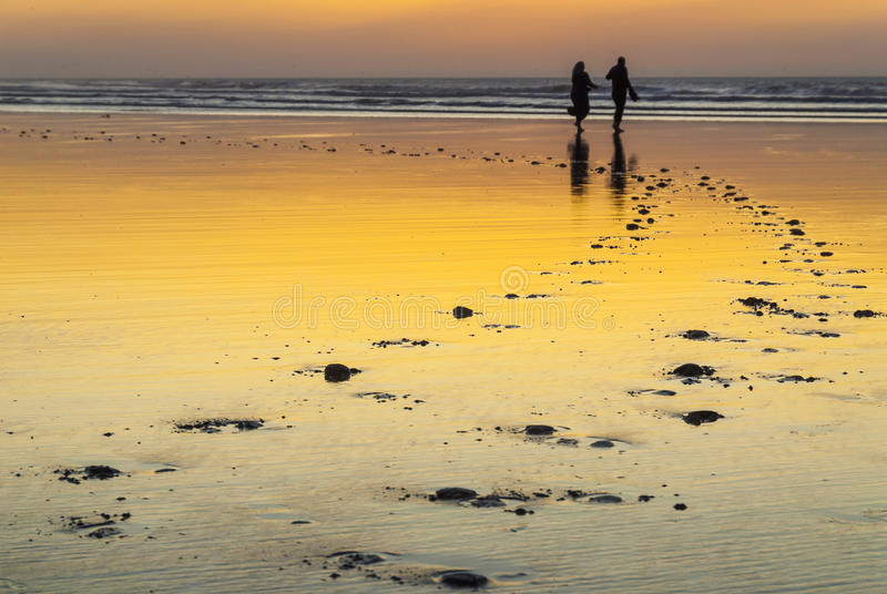 A Moroccan couple at the beach at sunset stock image