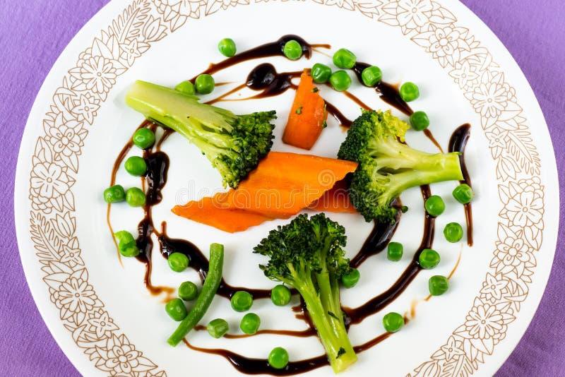 Morot, broccoli och ärtor på den vita plattan på violett bakgrund arkivfoto