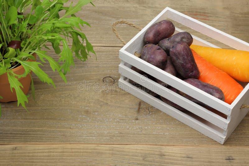 Morot och potatis i en ask på en träbakgrund royaltyfria foton