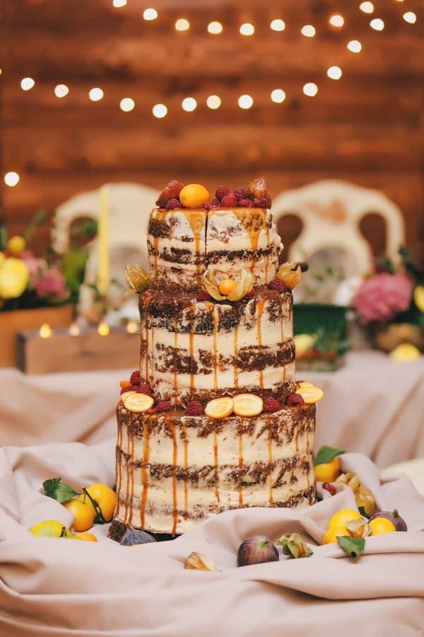 Morotbröllopstårtan med det öppna kexet dekorerade med citruns, apelsiner på en träbakgrund royaltyfri bild