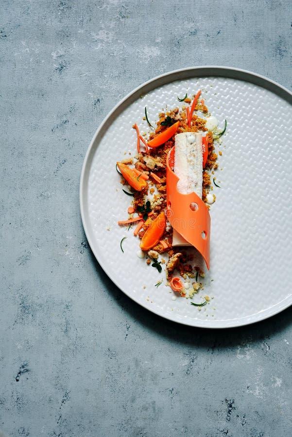 Morotefterrätt på en platta Högt kök Icke-standard matning Morotkaka med det kryddiga mous kexet, morottangeringelé och ost royaltyfri foto