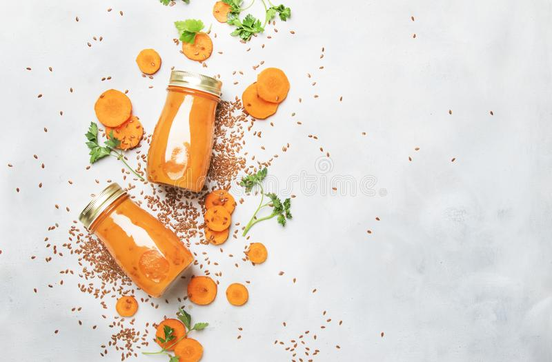 Morotfruktsaft eller smoothies med linfrö i glasflaskor, strikt vegetariandryck, den sunda drinken för rent rått bantar, den sele arkivfoto