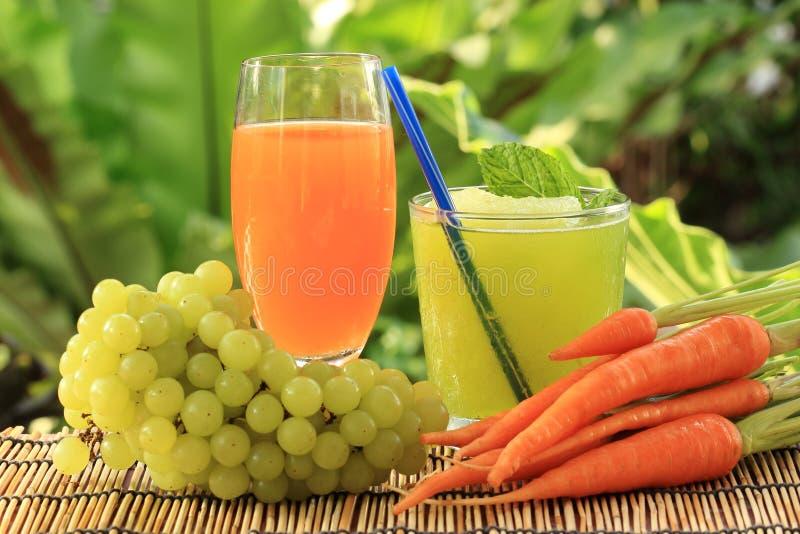 Morotfruktsaft och druvasmoothie royaltyfri bild