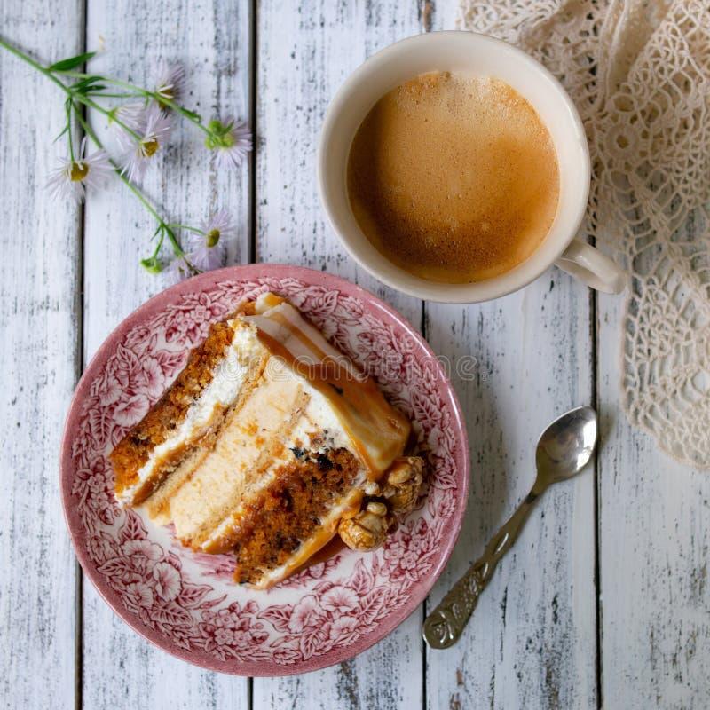 Morotkaka med den rimmade karamell- och ostkakainsidan som dekoreras med popcorn och karamell En skiva av kakan med en kopp kaffe royaltyfria bilder