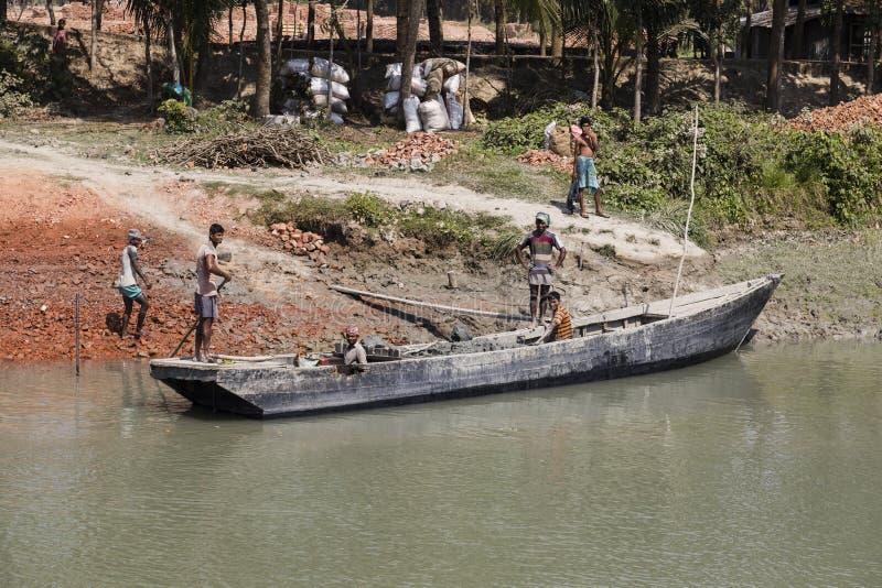 Morrelganj, Bangladesh, le 27 février 2017 : À la rive au Bangladesh, des briques sont déchargées d'un vieux bateau en bois photographie stock libre de droits