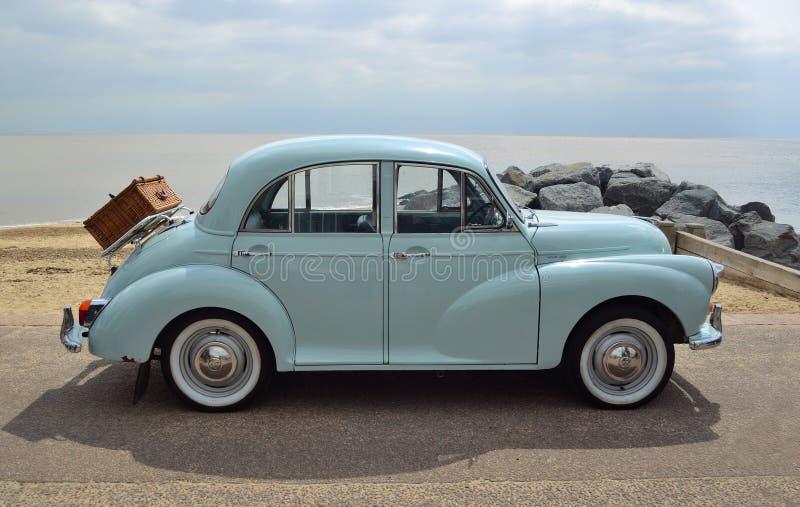 Morris Minor azul claro clásico con la cesta de la comida campestre parqueó en la 'promenade' de la orilla del mar fotografía de archivo libre de regalías