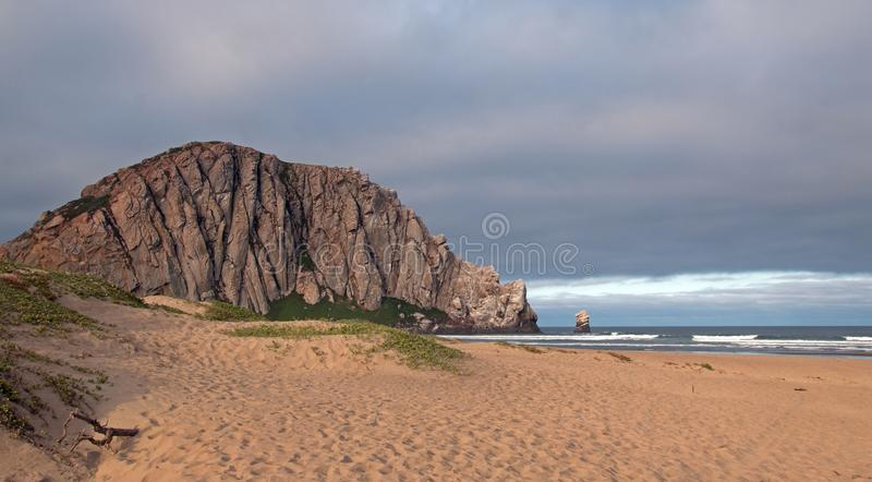 Morro Rock at sunrise under cumulus clouds at Morro Bay State Park camping spot on the Central California Coast USA. Morro Rock at sunrise under cumulus clouds royalty free stock photos