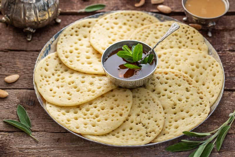 Morrocan薄煎饼Baghrir接近的看法用蜂蜜 免版税库存图片