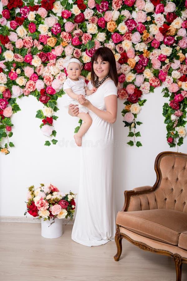 Mors dagskoncept - en lycklig vacker mor och hennes lilla dotter som ställer sig över blommornas bakgrund royaltyfri fotografi
