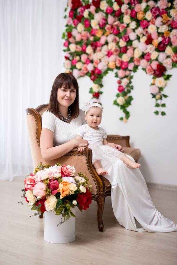 Mors dagskoncept - en lycklig, vacker mor och hennes söta lilla dotter som sitter på veterassoffan över blommornas vägg arkivfoto