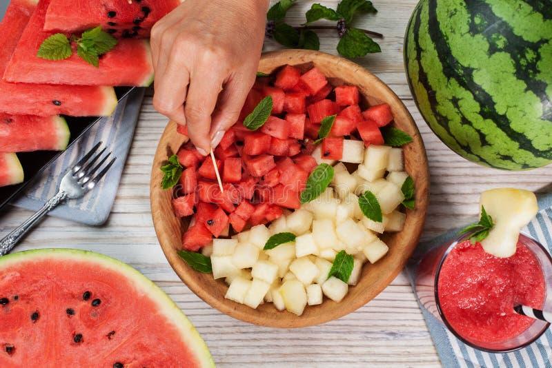 Morsi dell'anguria su un piatto Mano che seleziona uno spuntino sano di estate fotografia stock