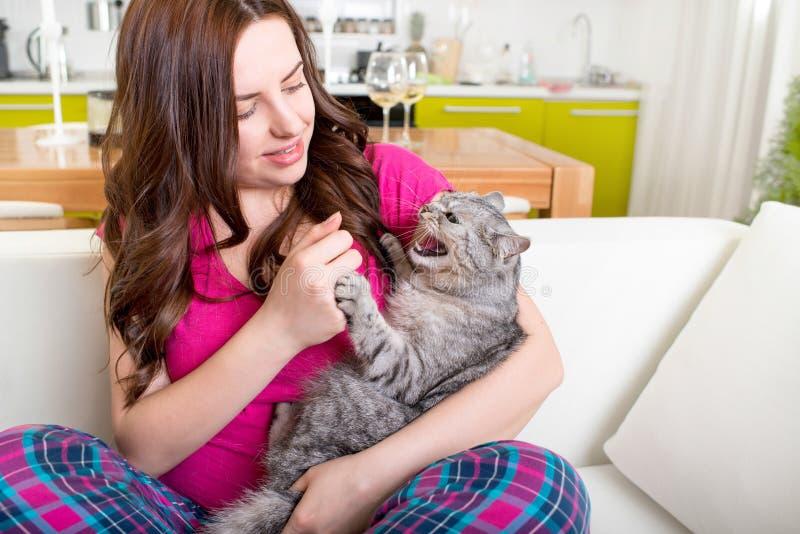 Morsures fâchées de chat avec la femme de griffes photographie stock libre de droits