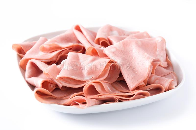 Mortadella slices on white plate isolated. On white background. Close up stock photography