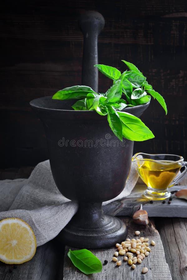 Mortaio con basilico, olio d'oliva, il limone ed i pinoli su una parte posteriore di buio fotografia stock libera da diritti