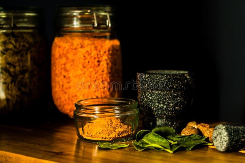 Mortaio e pestello con le foglie delle spezie e semi e barattoli delle lenticchie e della zizzania fotografie stock libere da diritti