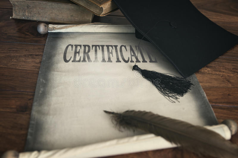 Mortar board and diploma, text certification. On scroll stock photography