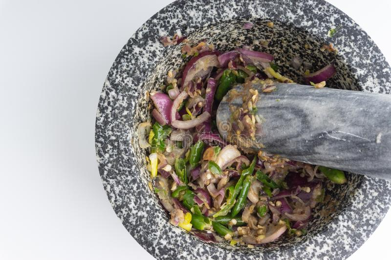 A mortar and pestle Lesung Batu. With mixed crushed chilies, shallots and anchovies on white background. Selective focus and crop fragment stock photos